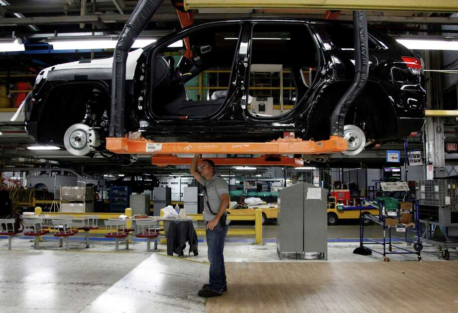FILE- In this Wednesday, May 8, 2013, file photo,  Jeff Caldwell, 29, right, a chassis assembly line supervisor, checks a vehicle on the assembly line at the Chrysler Jefferson North Assembly plant in Detroit.The Commerce Department issues its first estimate of how fast the U.S. economy grew in the April-June quarter on Wednesday, July 31, 2013.(AP Photo/Paul Sancya, File) ORG XMIT: NYBZ123 Photo: Paul Sancya / AP