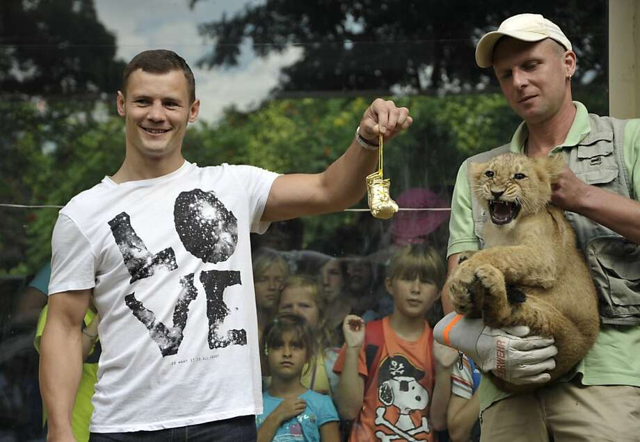 "Boxing's mane event:German boxer and current World Super Middleweight Champion Robert Stieglitz dangles tiny gold gloves in front of Roberta, prompting a growl from the 3-month-old baby lioness at Zoo Magdeburg in Germany. Stieglitz, who says that boxers who challenge him are stepping into ""literally the lion's den,"" is sponsoring the cub. Photo: Pauline Willrodt, AFP/Getty Images"