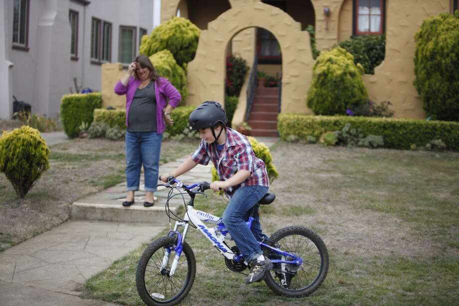 Patrick Martin (foreground), 11, of San Francisco, rides his bicycle as his mother, Julie Martin (background) watches in front of their home on Tuesday, July 23, 2013  in San Francisco, Calif. Photo: Lea Suzuki, The Chronicle