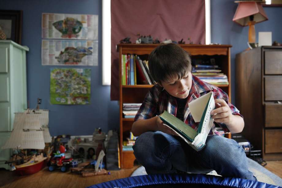 Patrick Martin, 11, of San Francisco, pages through a favorite book in his room on Tuesday, July 23, 2013 in San Francisco, Calif. Early therapy helped Patrick learn to read when he had difficulty and it is now a favorite activity. Photo: Lea Suzuki, The Chronicle