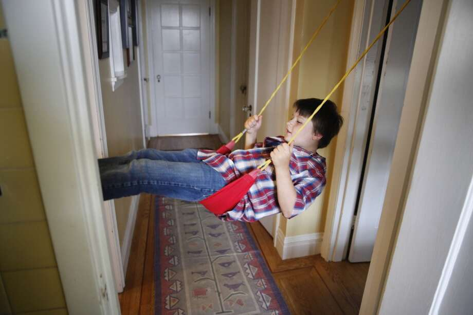 Patrick Martin (right), 11, of San Francisco, passes by a doorway as he swings on a swing hanging in his doorway on Tuesday, July 23, 2013 in San Francisco, Calif.  Patrick has sensory processing disorder and the swing helps calm him. Photo: Lea Suzuki, The Chronicle