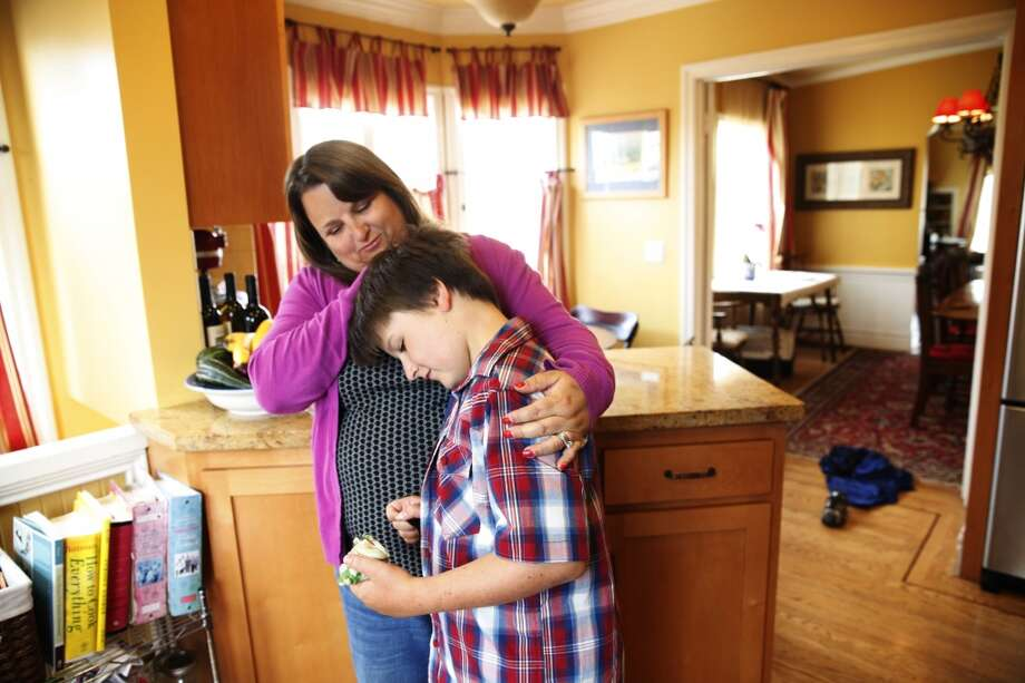 "Patrick Martin (right), 11, of San Francisco, holds a ""fidget"" as he gets a hug from his mother Julie Martin (left) as they stand in their kitchen on Tuesday, July 23, 2013 in San Francisco, Calif.  Patrick has sensory processing disorder and the ""fidgets"" help keep him calm and focused and distracts him from upsetting sensations. Photo: Lea Suzuki, The Chronicle"