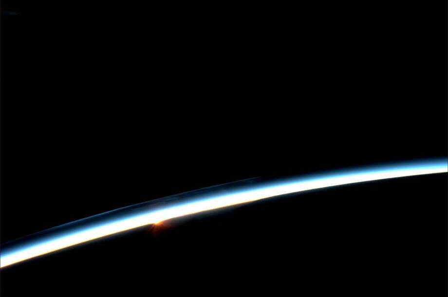 """""""First hint of sunrise is blue. Then red creeps in."""" - Karen Nyberg, July 30, 2013. The space station orbits Earth every 90 minutes at a rate of about 17,500 miles per hour. So the crew sees about 16 sunrises and sunsets a day, says NASA. Photo: Karen Nyberg, International Space Station"""