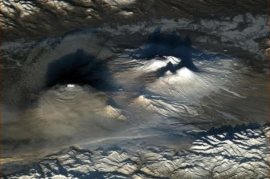 """Volcanoes look dramatic at dawn. They startled me when I spotted them through the lens."" - Chris Hadfield, over Russia, 2013.  Photo: Chris Hadfield, Internationship Space Station"
