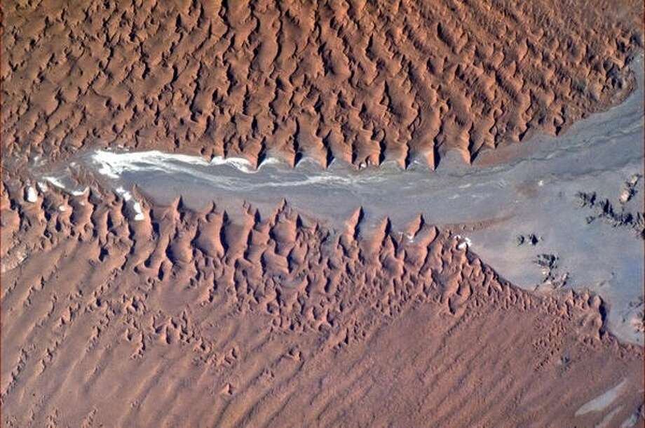 """Frozen crests of sand break over the arid rock, Namibian coast, Africa"" - Chris Hadfield, 2013.  Photo: Chris Hadfield, Internationship Space Station"