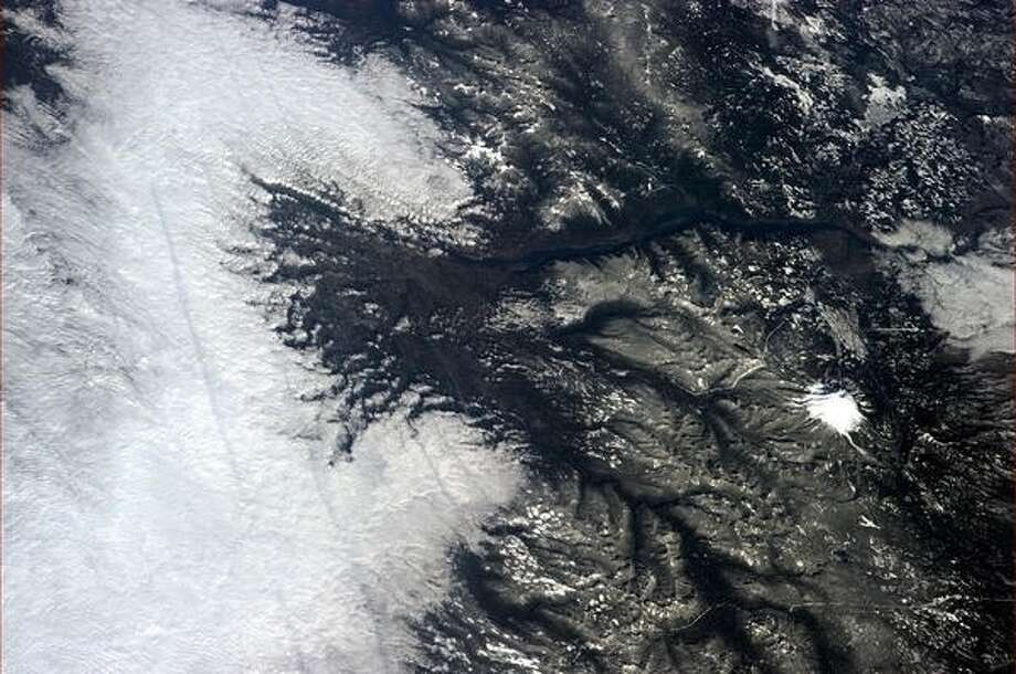 """An old volcano river, gorge and fog - where could this be? Hint: I think I see Zigzag ..."" - Chris Hadfield, 2013. (It's Mt. Hood, Oregon).  Photo: Chris Hadfield, Internationship Space Station"