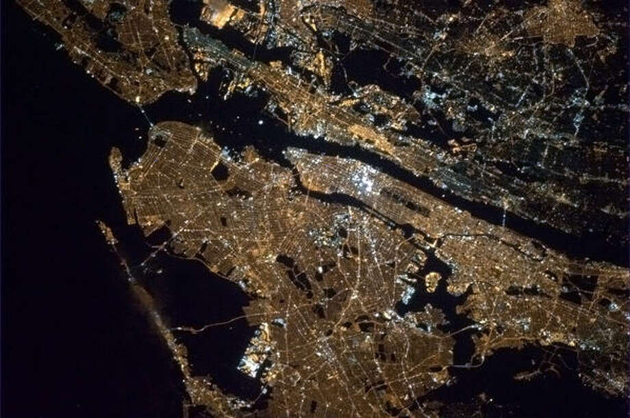 add New York City, lit up like a bulb. The Statue of Liberty is clearly visible in the night from above Chris Hadfield from the International Space Station. march 2013 Photo: Chris Hadfield, Internationship Space Station