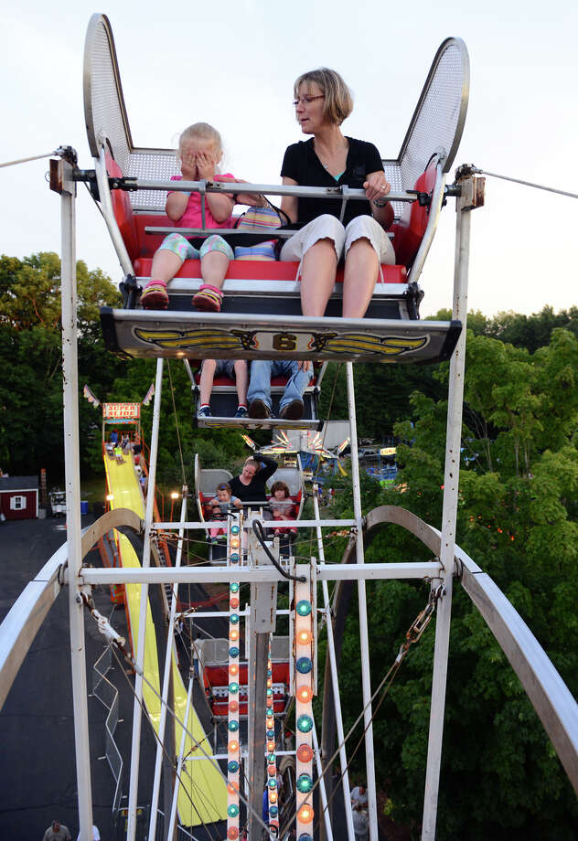 Lindsey Civitelli, 4, of Newtown, is afraid to look while at the top of the Ferris Wheel with her mom Jessica Marlin at the 78th Annual Easton Fireman's Carnival in Easton, Conn. on Wednesday July 31, 2013. The carnival continues nightly 6pm-11pm through Saturday August 3, 2013. To see more photos go to ctpost.com. Photo: Christian Abraham / Connecticut Post