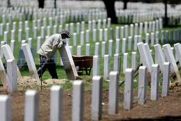 Lucio Rojo works to level a headstone at Fort Sam Houston National Cemetery, Wednesday, July 31, 2013, in San Antonio. The cemetery is in the process of raising and realigning more than 35,000 headstones and installing about 2.5 million square feet of sod.