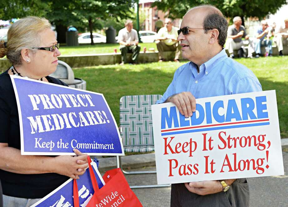 Gail Myers, left, of Glenville and Michael Burgess of Delmar during a rally for Medicare on the anniversary of its 1965 passage at West Capitol Park in Albany, N.Y., Wednesday July 31, 2013.  (John Carl D'Annibale / Times Union) Photo: John Carl D'Annibale / 00023336A