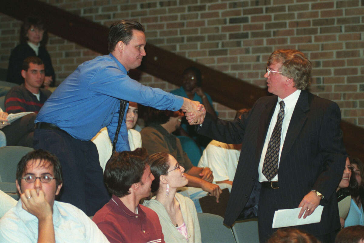 Darryl Santell (left), a student at College of the Mainland, congratulates Professor David Michael Smith during a 2005 meeting on Smith gaining tenure.