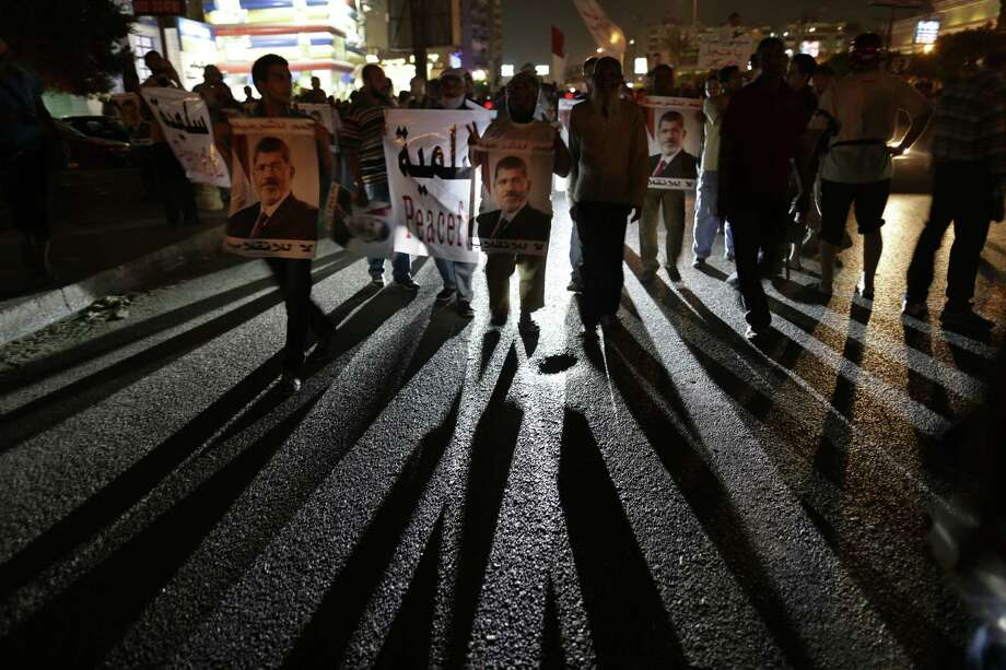 Supporters of ousted Egyptian President Mohammed Morsi chant slogans this week in Cairo's Nasr City, home to one of two sprawling sit-in sites that the military-backed interim government wants broken up. Photo: Hassan Ammar / Associated Press