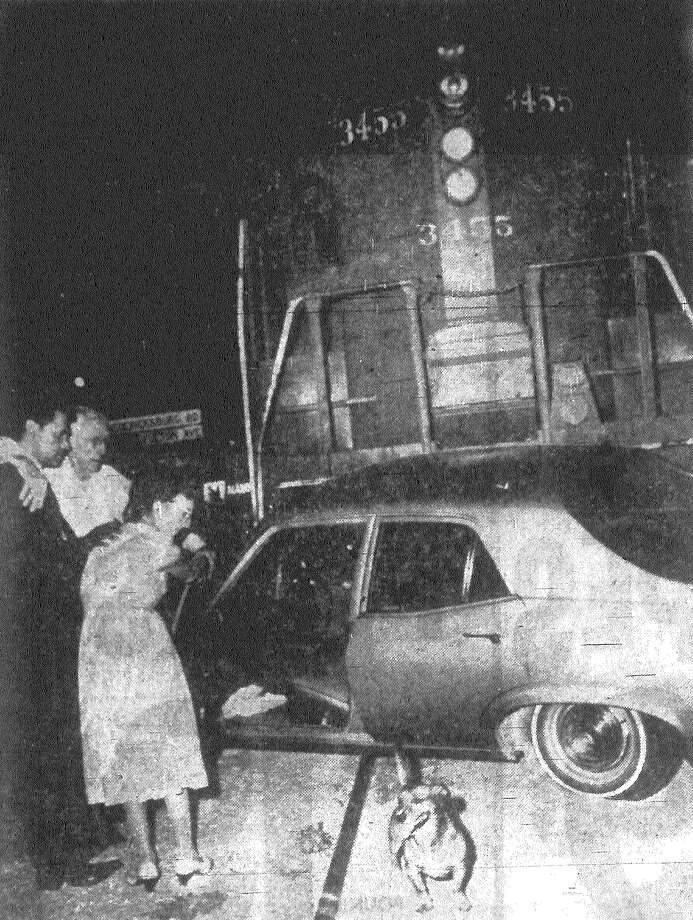 A.E. Kinder, 85, and Esther Davis, 65, are assisted after they crawled from their car after being struck by a 28-car Southern Pacific freight train at Fredericksburg Road and the SP tracks near Woodlawn Avenue. Although the train pushed their car some 130 feet, the two left the Santa Rosa Hospital without being treated. Police said the train was going about 18 miles per hour and that witnesses said a traffic signal at the crossing was working. Published in the San Antonio Express Aug. 22, 1968. Photo: File Photo