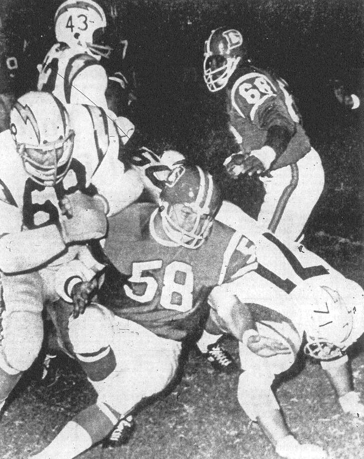 San Diego halfback Jim Tolbert (43) breaks up the middle on a kickoff return following Denver's field goal in their exhibition game at Alamo Stadium. Charger linemen Bob Briggs (68) and Harold Akin (71) help clear the way by taking out Bronco linebacker Frank Richter (58). Tolbert eluded Denver's Curly Culp (66) to make it back to the Charger 28-yard line, but the return was nullified by a clipping penalty. Published in the San Antonio Express Aug. 31, 1968. Photo: File Photo