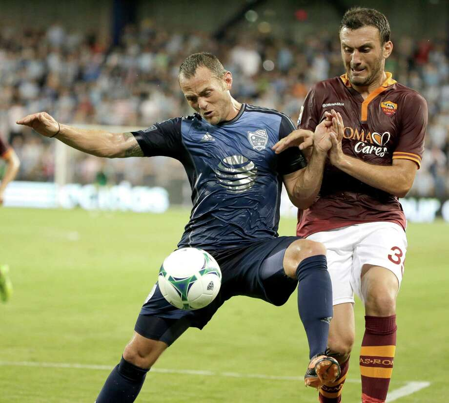 The Dynamo's Brad Davis, left, fights for possession with AC Roma's Vasilis Torosidis during the MLS All-Stars' 3-1 loss to the Italian team. Photo: Charlie Riedel, STF / AP