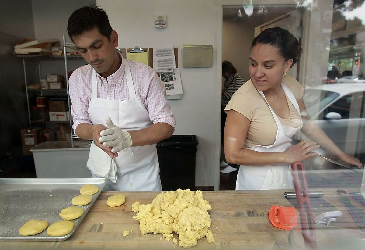 Alexander Bustos, who has been with the program for the past four months, is helped by Martha Martinez, while preparing cornmeal biscuits at Hayes Valley Bakeworks in San Francisco, Calif. on Wednesday July 31, 2013. The non-profit Toolworks program, which trains and employ homeless, disabled and at-risk individuals, is celebrating their one year anniversary since the opening of the Hayes Valley Bakeworks, where men and women are taught how to prepare gourmet foods.