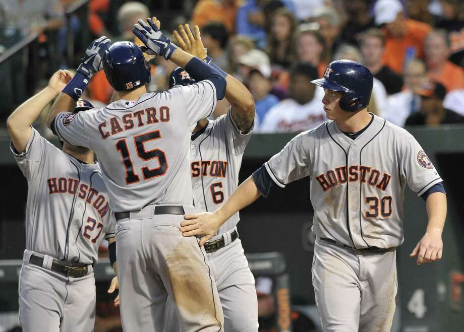 Houston's Jason Castro is greeted by teammates after hitting a grand slam in the fourth inning. Photo: Gail Burton / Associated Press