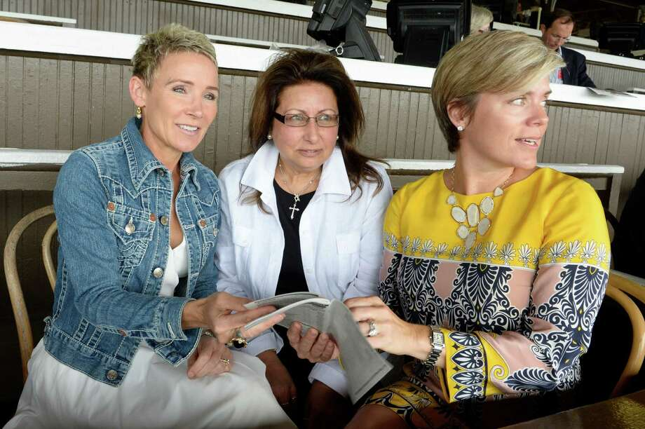 The Starladies Racing members: Donna Barton Brothers, left, Barbara Lucarelli, center, and Lauri Wolf, right, look over the program Sunday July 28, 2013, at Saratoga Race Course in Saratoga Spings, N.Y. (Skip Dickstein/Times Union) Photo: SKIP DICKSTEIN