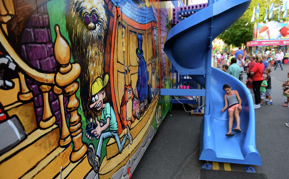 "Logan Pastor, 10, slides out of the ""Whacky Shack"" funhouse at the 78th Annual Easton Fireman's Carnival in Easton, Conn. on Wednesday July 31, 2013. The carnival continues nightly 6pm-11pm through Saturday August 3, 2013. Photo: Christian Abraham / Connecticut Post"