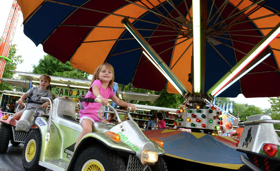 Lucy Roth, 3, of Trumbull, enjoys a kiddie ride at the 78th Annual Easton Fireman's Carnival in Easton, Conn. on Wednesday July 31, 2013. The carnival continues nightly 6pm-11pm through Saturday August 3, 2013. Photo: Christian Abraham / Connecticut Post