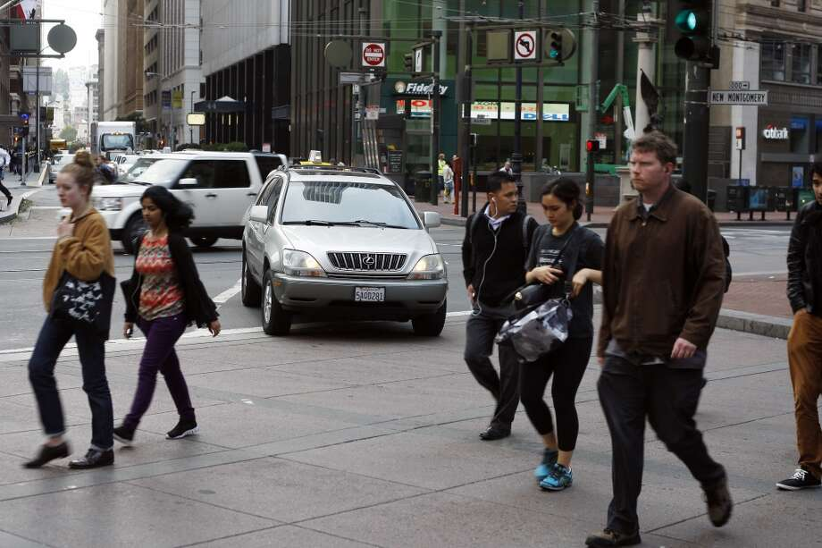 Pedestrians cross the road on the walk signal while a car waits to clear the middle of Market St at the intersection of New Montgomery and Market Street on Tuesday, July 30, 2013 in San Francisco, Calif. Photo: Rohan Smith, The Chronicle