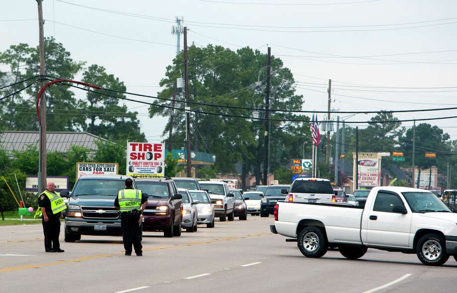 The Harris County Sheriff's Department diverts traffic at the scene of an accident after a car collided with a pedestrian in the 5000 block of Louetta Road near Kuykendahl Road, Thursday, Aug. 1, 2013, in Spring. HCSD Deputy Dan Drake said the driver showed no signs of intoxication or impairment after he failed to see the pedestrian, who attempted to cross from the South side to the North side of Louetta, because he said the roadway was dark. Two nurses on their way to work stopped to render aid to the pedestrian until life flight arrived where he was transported to Hermann in critical condition. Photo: Cody Duty, Houston Chronicle / © 2013 Houston Chronicle