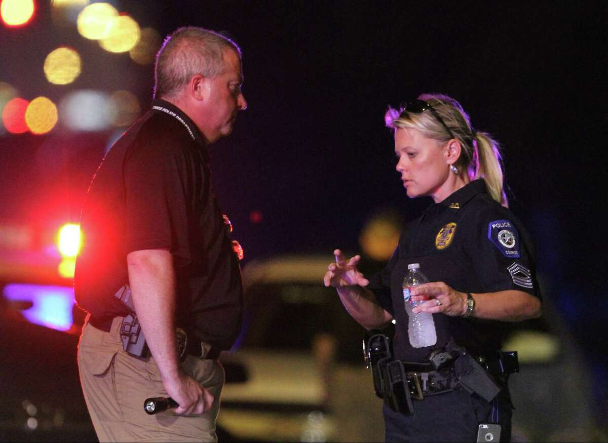 Sgt. Dorcy Riddle works a crime scene after an off-duty officer with the Conroe Police Department shot and killed an alleged shoplifter near the Conroe Walmart on North Loop 336 Wednesday, July 31, 2013. (AP Photo/ The Courier, Jason Fochtman)