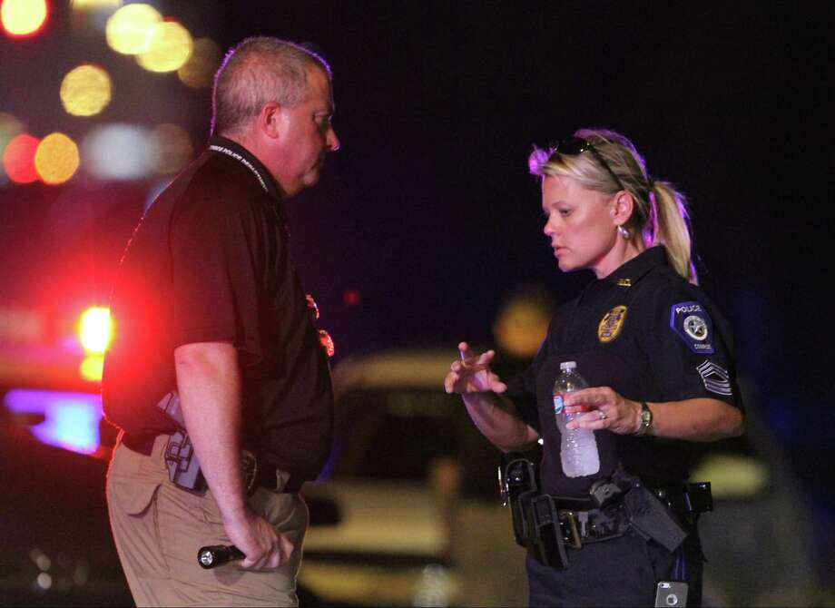 Sgt. Dorcy Riddle works a crime scene after an off-duty officer with the Conroe Police Department shot and killed an alleged shoplifter near the Conroe Walmart on North Loop 336 Wednesday, July 31, 2013. (AP Photo/ The Courier, Jason Fochtman) Photo: Jason Fochtman, Associated Press / Conroe Courier