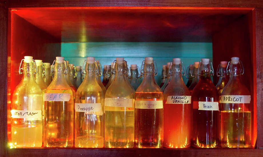 Flavor infused tequila are lined up behind the bar at El Gran Malo. Photo: Brett Coomer, Houston Chronicle / 2011 Houston Chronicle