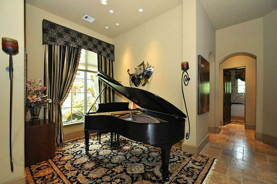 Inviting piano room w/piano lighting, custom draperies & views of the lush courtyard.	