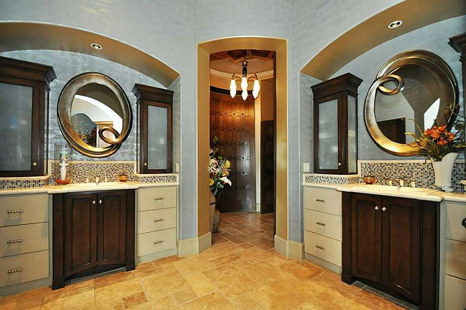 Custom designed sinks & vanities compliment this resort style bathroom. Dual closets w/washer/dryer inside, custom makeup lighting & extensive storage & pull-downs make this bathroom a dream.See the listing here.