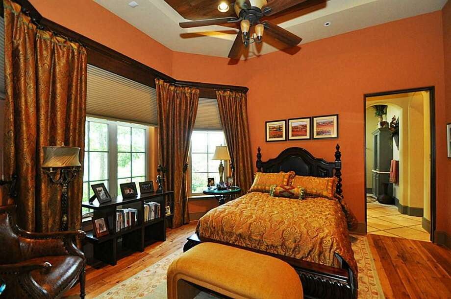 In-law suite bedroom features wood flooring, custom draperies & views of the water.	