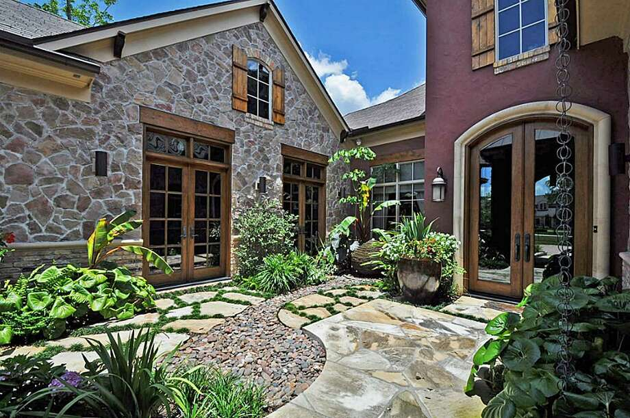Courtyard features lush landscaping and leads to custom glass front doors.		