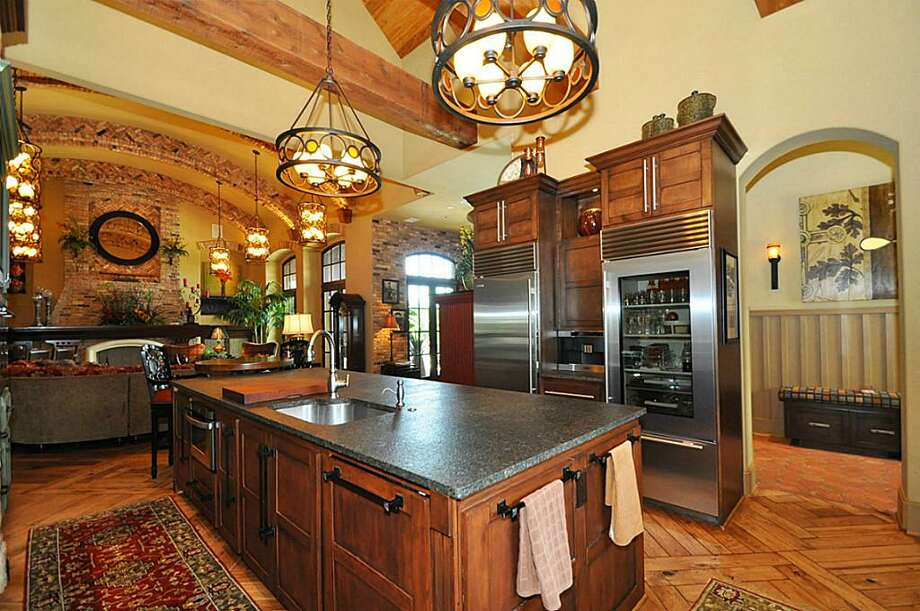 Stainless steel dual refrigerators, dual ovens, & more open to grand foyer for entertaining.See the listing here.