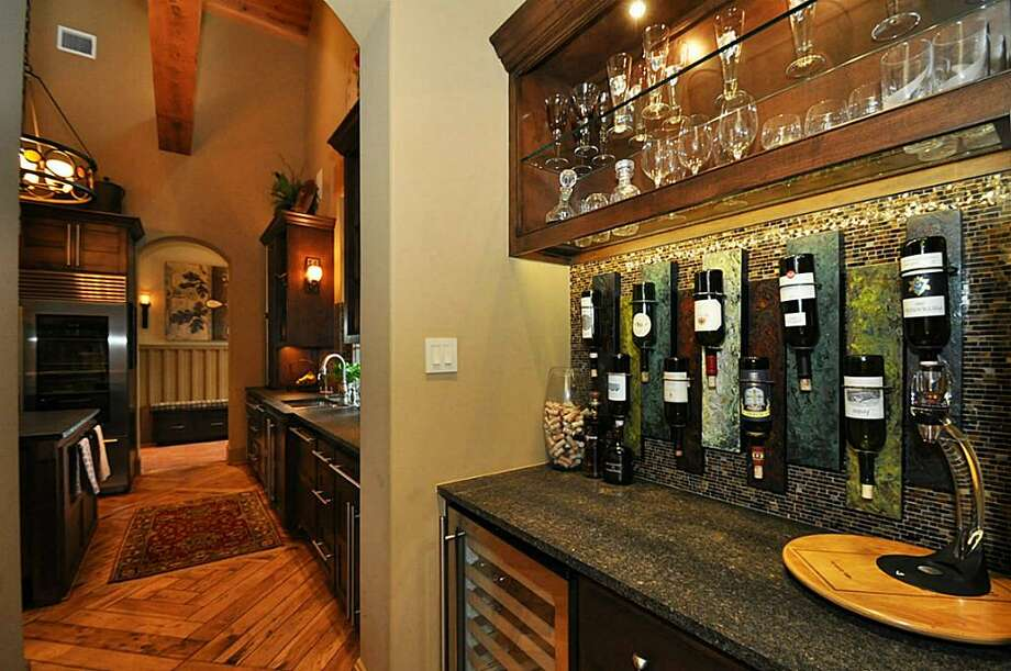 Wine bar & pantry adjacent to the kitchen feature wine refrigerator, granite counters & custom stained glass.	