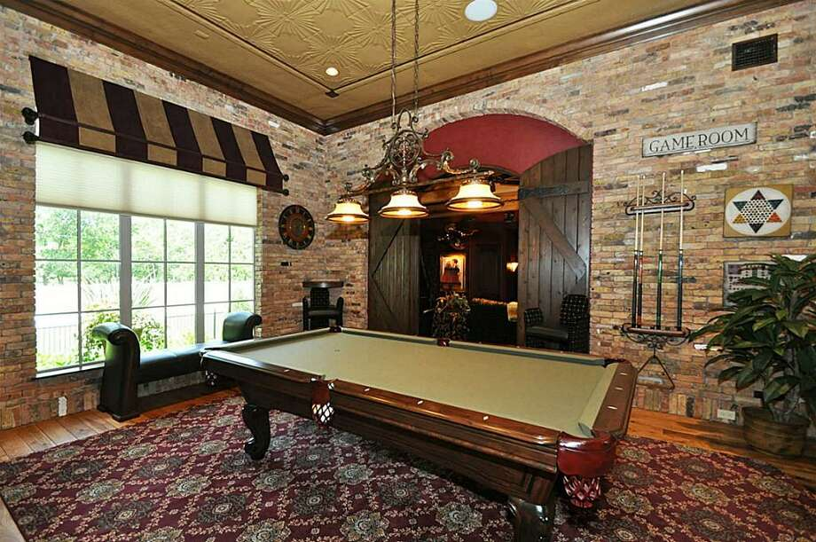 Billiards room features custom a custom tin ceiling, 3 media centers for sports viewings, pecan wood floors, game room storage & leads into the private theatre.	