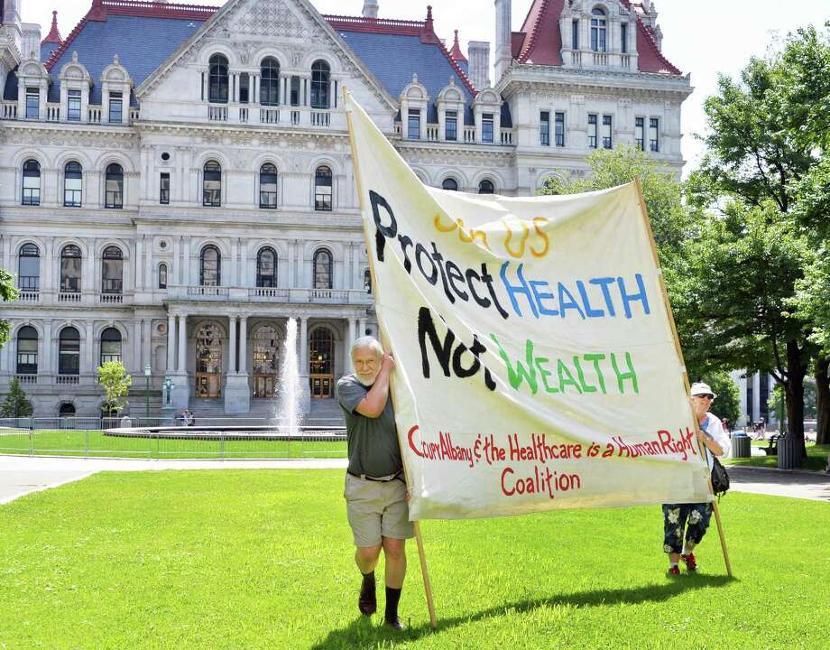 Thomas Heckman, left, of East Schodack, and his wife Lesley Tabor carry a large banner to a rally for Medicare on the anniversary of its 1965 passage at West Capitol Park in Albany, N.Y., Wednesday, July 31, 2013.  (John Carl D'Annibale / Times Union) Photo: John Carl D'Annibale / 00023336A
