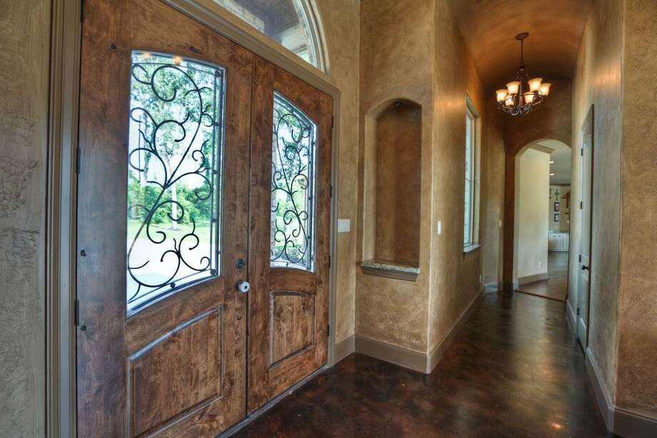 The home's entry comes with barreled ceilings, custom paint, fabulous fixtures and solid wood w/wrought iron inlays.See the listing here