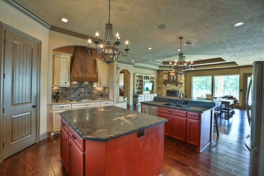 The chef of the family will have zero complaints about this kitchen. It features a large island, walk in pantry, double ovens, built in microwave, stainless steel appliances, granite counter tops, slate backsplash and custom cabinets.