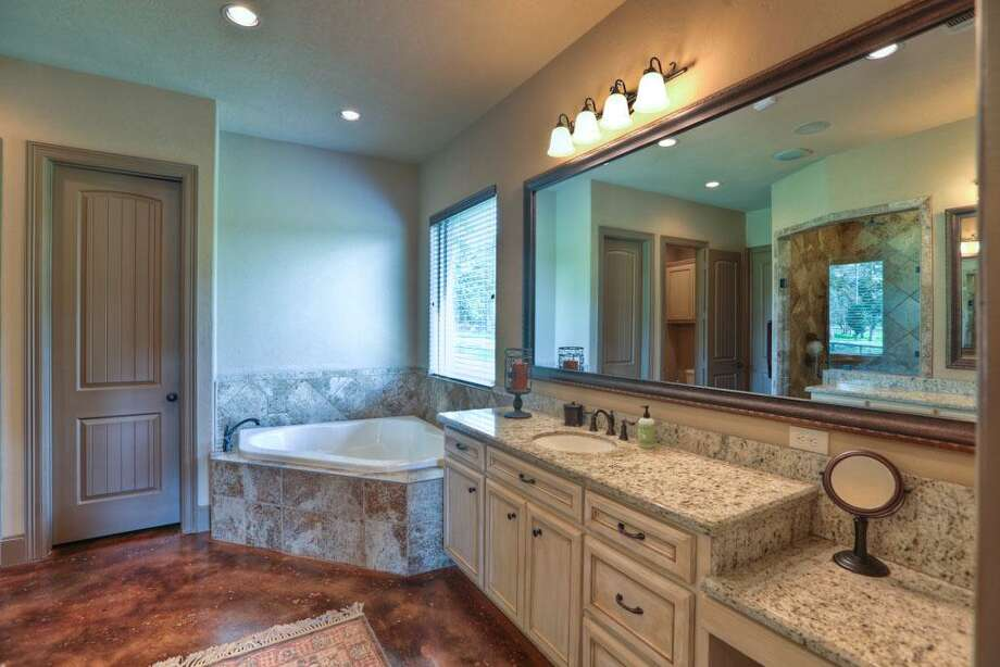 The master bath has double sinks with vanity, granite tops, custom framed mirrors, garden tub and his and hers closets.