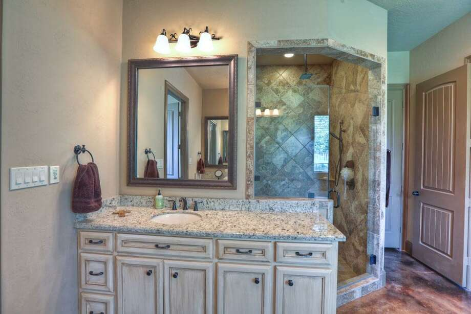 Decorative fixtures are beautifully tied into the master bathroom. It comes with two tankless hot water heaters.	