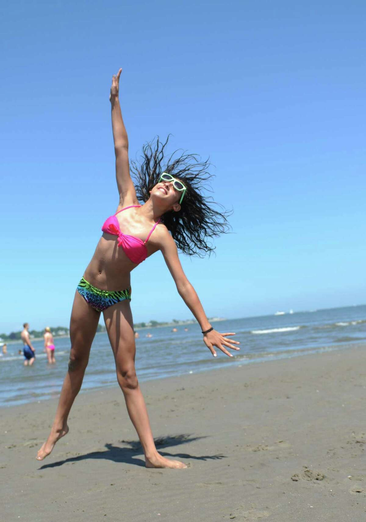 A young girl turns cartwheels on a hot holiday Wednesday, July 4, 2013 at Silver Sands State Park in Milford, Conn.