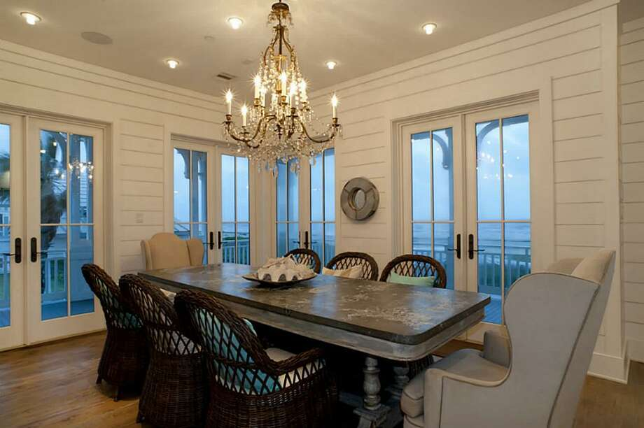Beach front Gulf views continue in the exquisite dining room with the antique Belgian crystal chandelier and custom zinc top antique table from Vieux.