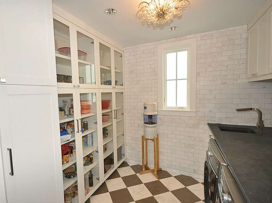 Butler's Pantry with custom marble and Lagos Azul floor. GE profile French Door refrigerator/freezer (not in picture) and Kenmore Elite front loading washer and dryer. Glass pantry cabinets and laundry sink.