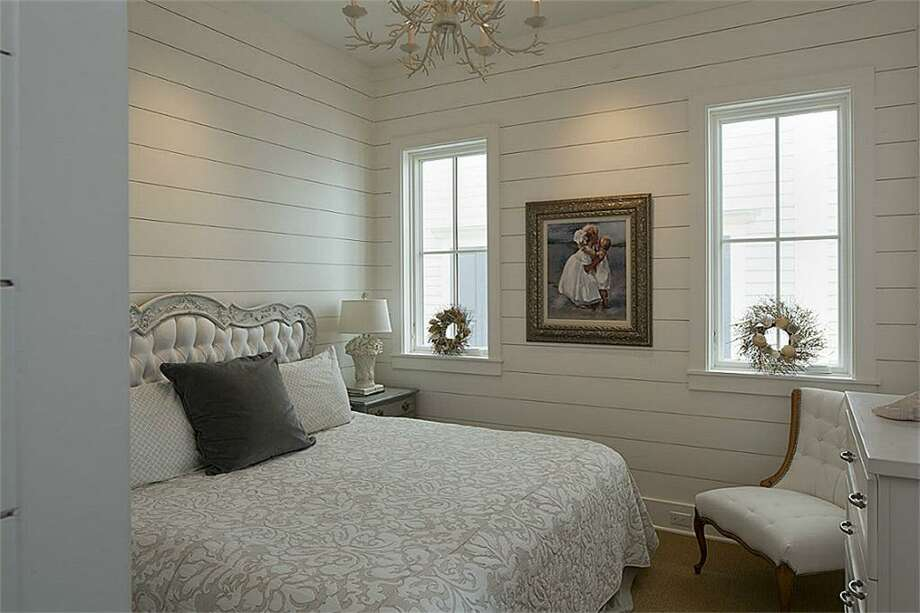 "Second floor guest bedroom with built in dresser and drawers in closet; king size bed with antique headboard; wall-mounted Samsung 42"" flat screen plasma TV; built in cabinet and bookshelves.