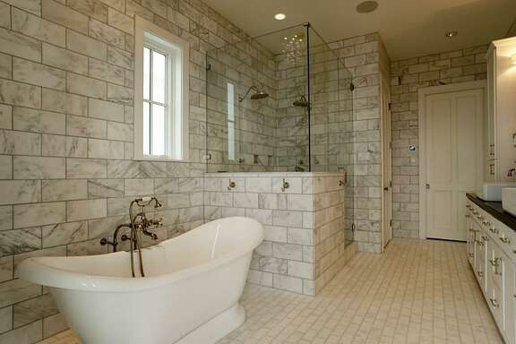 Luxurious master bath with ocean views; floor-to-ceiling Carrera marble tile; pedestal tub; large shower with 2 rainfall shower heads, hand shower & body jets; large walk-in closet with custom drawers, pull-down racks, pegboard & full-length mirror.     See the listing here
