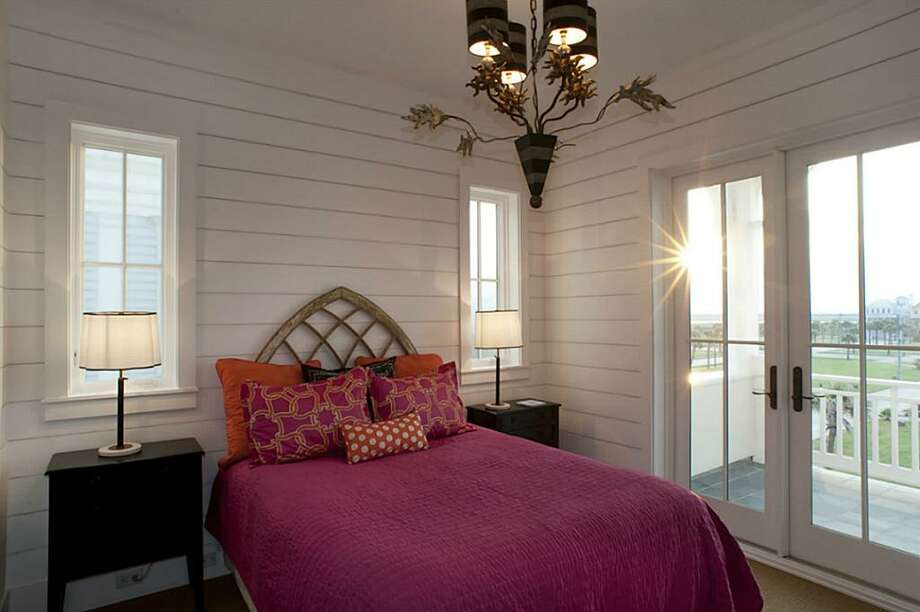 Third floor Northwest bedroom provides village views; built-in queen bed with drawers underneath; New Orleans artist-designed chandelier; custom closet w/ built-in drawers & pull down rack; En-suite bathroom.