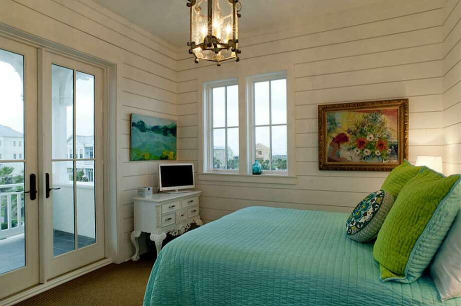 Ocean & Village Views from the 3rd floor Northeast Bedroom with built-in queen bed with drawers underneath; custom closet w/ built-in drawers & pull down rack; custom light fixture from Brown; double French doors; En-suite bathroom.