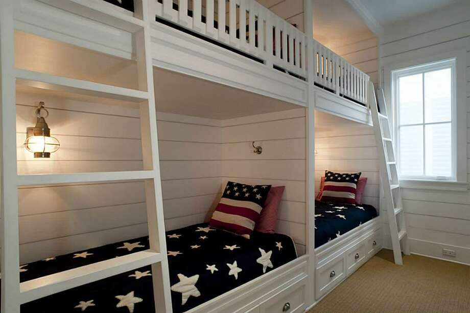 """Third floor bunk room with 4 built-in bunk beds w/ lanterns and built-in drawers underneath bottom bunks. Built-in dresser; custom closet w/ built-in drawers & pull-down rack; wall mounted Toshiba 24"""" LED HDTV w/ built-in DVD player; En-suite bathroom.See the listing here"""