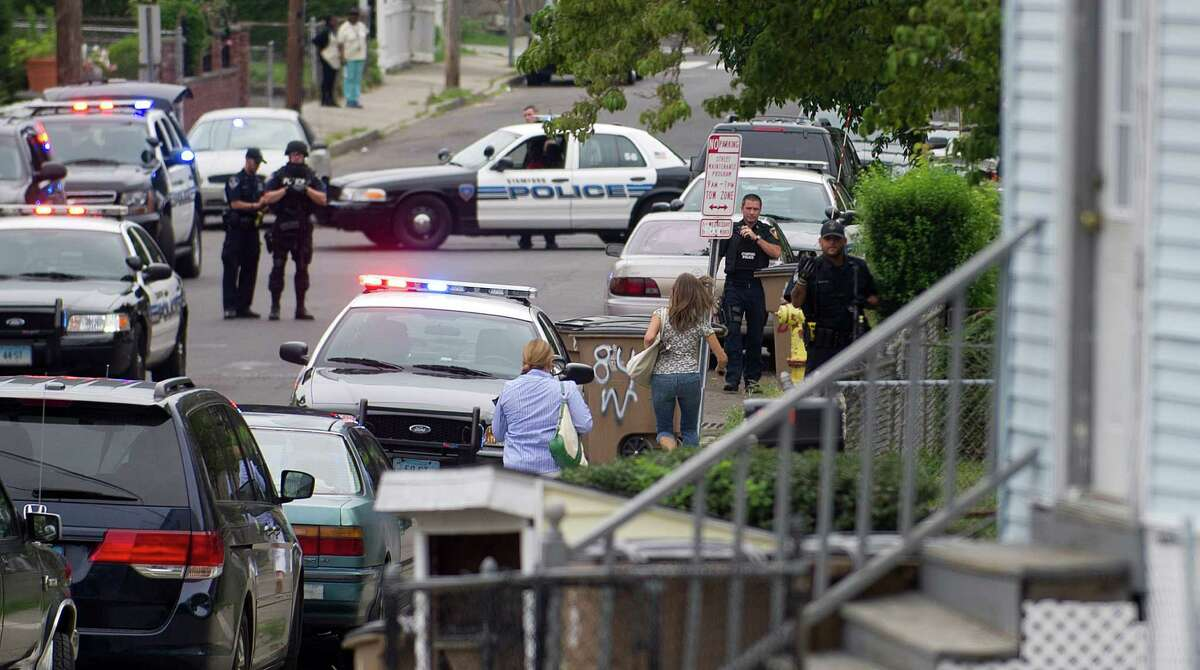 Two women run toward police officers who were responding to a house they were in where it was reported a possibly suicidal man with a gun was inside at 100 Warren Street in Stamford, Conn., for a report of a man with a gun on Thursday, August 1, 2013.